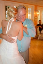 A father holds his daughter and bride tight with love and pride