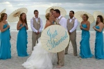 Bridesmaids in their turquoise water blue dresses and groomsmen in their beach colored ware cheer on the bride and groom