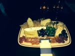 Plate of heeses, meats, olives, bread and wine enjoyed rooftop