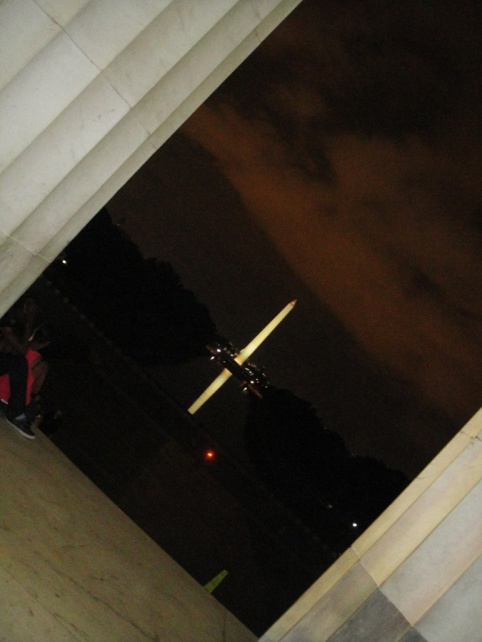 The Washington Monument all lit up at night and reflecting in the Lincoln Memorial Reflecting Pool