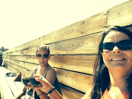 Two gals enjoying a glass of wine rooftop in Brooklyn