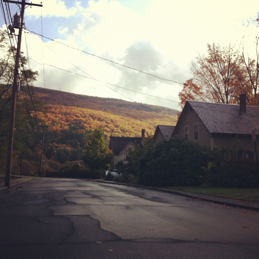 The view through the front window of a 2012 jet black Camaro as my daughter and I wind our way through the Vermont Countryside