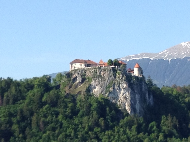A medieval castle sits perched atop a rock outcropping in the Slovenia countryside