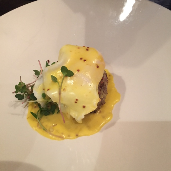 Savannah Style Crab Cake - smothered with poached local egg, pea greens and dijon mustard on Chaz at the Plaza, KC.