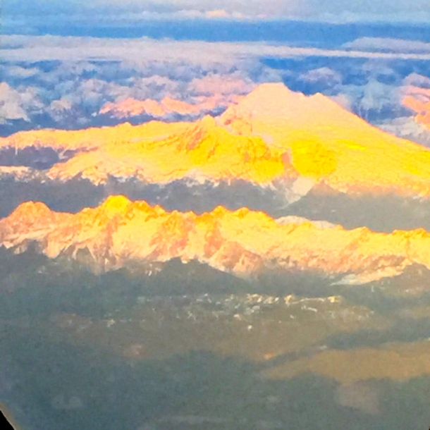 Snowcapped mountains north of Vancouver bathed in the light of the setting sun.