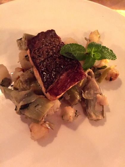 Wild striped bass served on a bed of artichokes, roasted potatoes and onions.