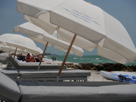 Large beach umbrellas give shade to double wide loungers to give shade along the beaches of Naples