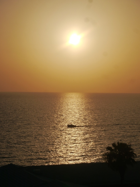 The sun setting over the Gulf, with a little fishing boat out enjoying the beautiful setting catching more fish while catching the last rays of sun.