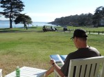 My husband reading while looking out over the 18th green at Pebble Beach.