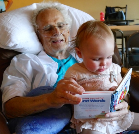 Great-grandpa reading to his great-granddaughter.